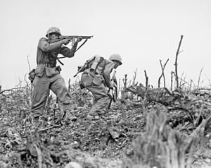 A Marine from the 2nd Battalion, 1st Marines on Wana Ridge provides covering fire with his Thompson submachine gun, 18 May 1945. (Wikipedia)